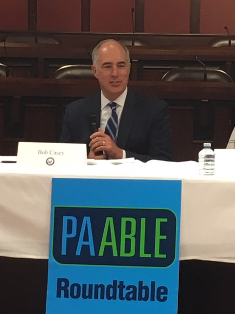 Senator Casey at table with white cloth and sign reading PA Able Roundtable